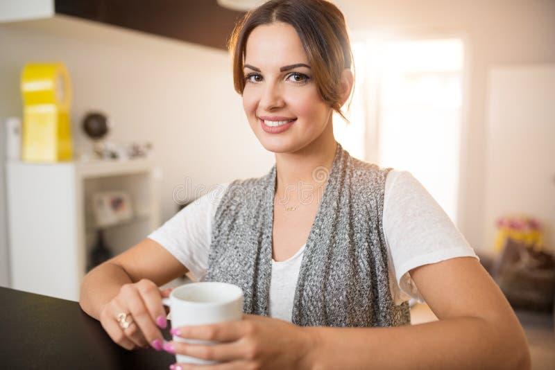 Frau, die am Zähler mit Tasse Tee steht lizenzfreies stockbild