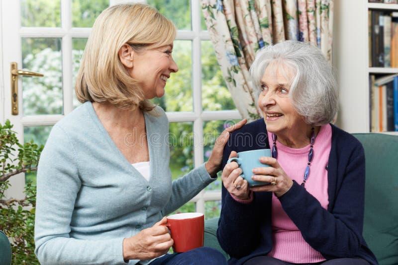 Frau, die Zeit nimmt, älteren weiblichen Nachbar zu besuchen und zu sprechen stockfoto