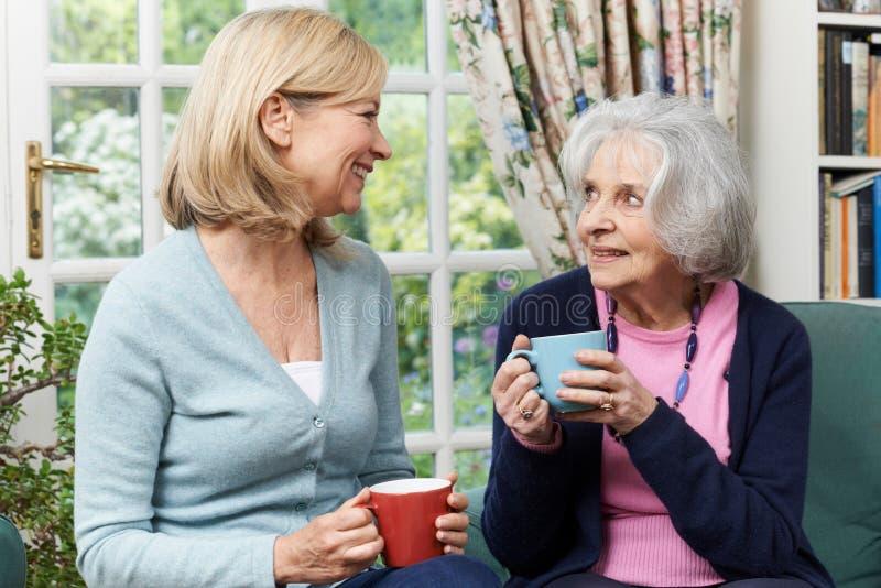 Frau, die Zeit nimmt, älteren weiblichen Nachbar zu besuchen und zu sprechen stockbild