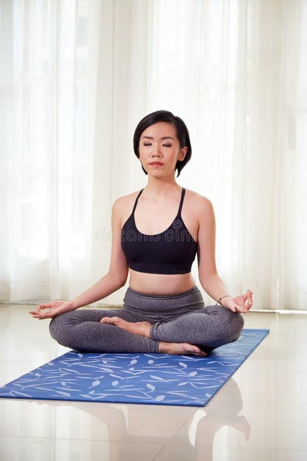 Frau, die zu Hause auf dem Boden meditiert stockbilder