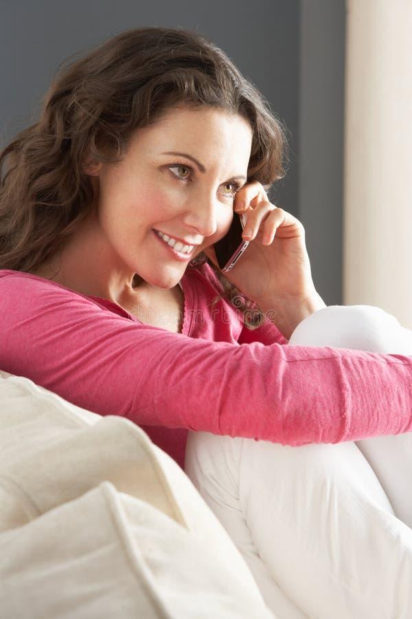 Frau, die zu Hause auf dem Sofa spricht am Telefon sitzt stockbilder