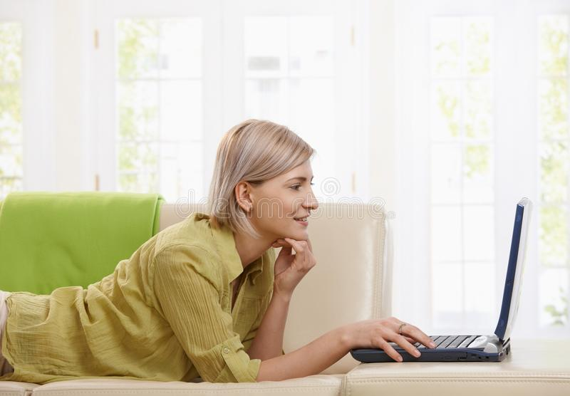Frau, die zu Hause Computer verwendet stockbild
