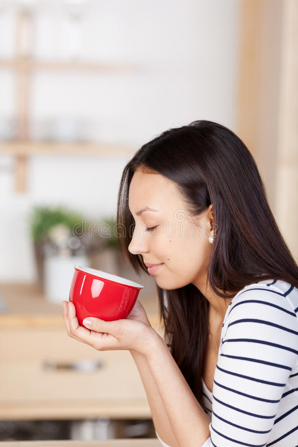 Frau, die zu Hause das Aroma des Kaffees genießt lizenzfreie stockfotos