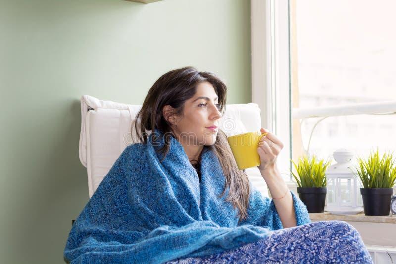Frau, die zu Hause, in der Hand denkend mit Tee sitzt stockbild