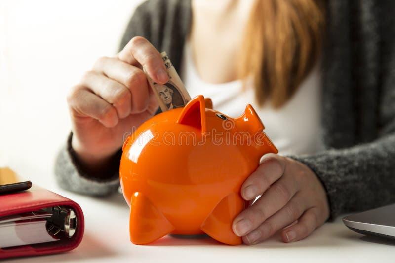 Frau, die zu Hause Dollarschein in ein Sparschwein im livin einfügt stockfoto