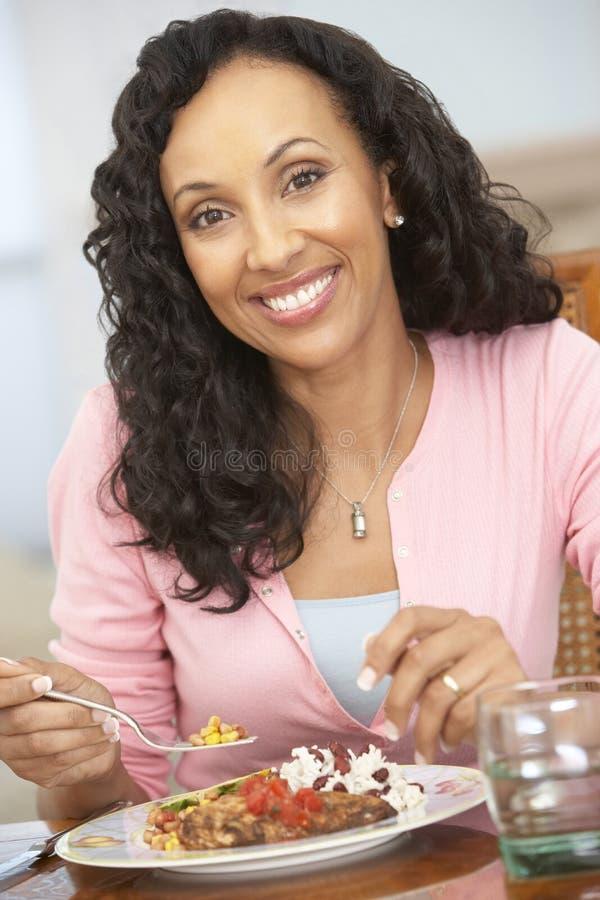 Frau, die zu Hause eine Mahlzeit genießt stockbilder