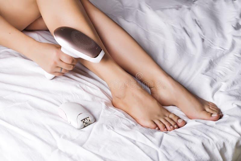 Frau, die zu Hause Haar mit spezieller Ausrüstung auf einem Bett entfernt lizenzfreie stockfotos