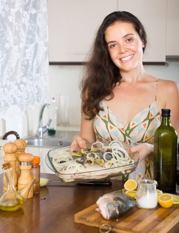Frau, die zu Hause Küche der Fische kocht lizenzfreie stockbilder