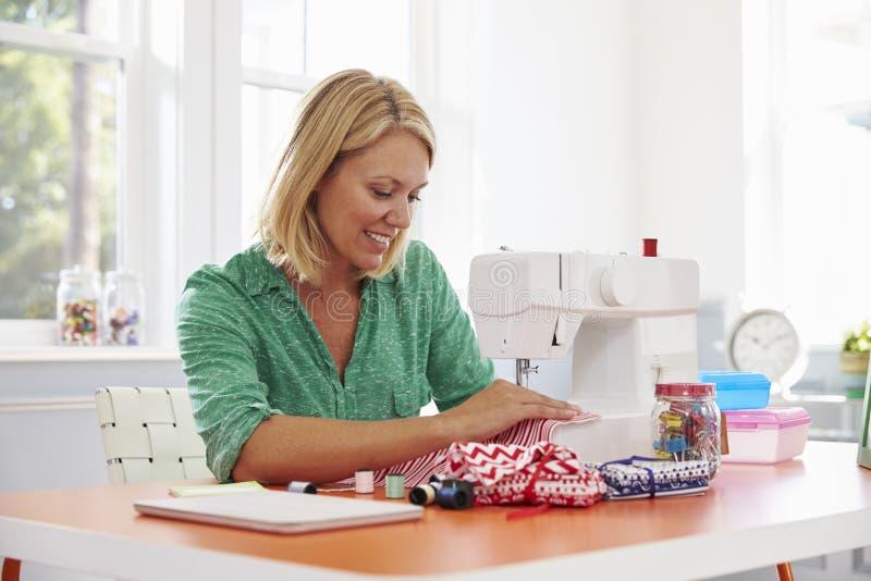 Frau, die zu Hause Kleidung unter Verwendung der Nähmaschine herstellt lizenzfreies stockfoto