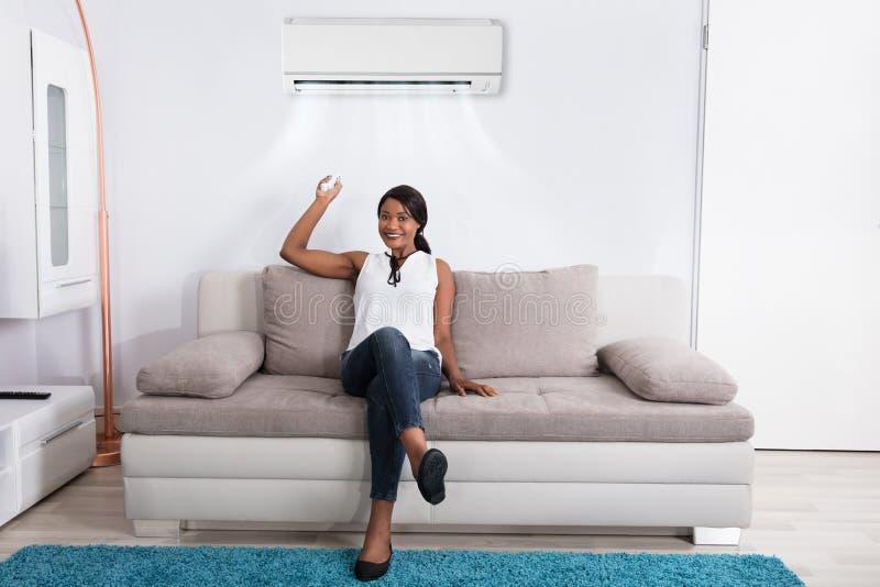 Frau, die zu Hause Klimaanlage verwendet stockbild