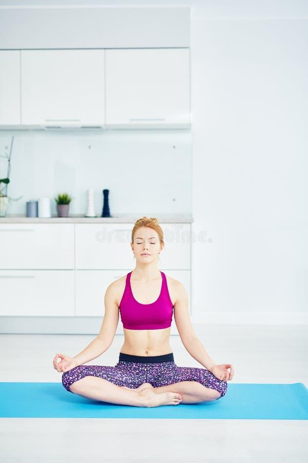 Frau, die zu Hause in Lotus Pose sitzt stockbild