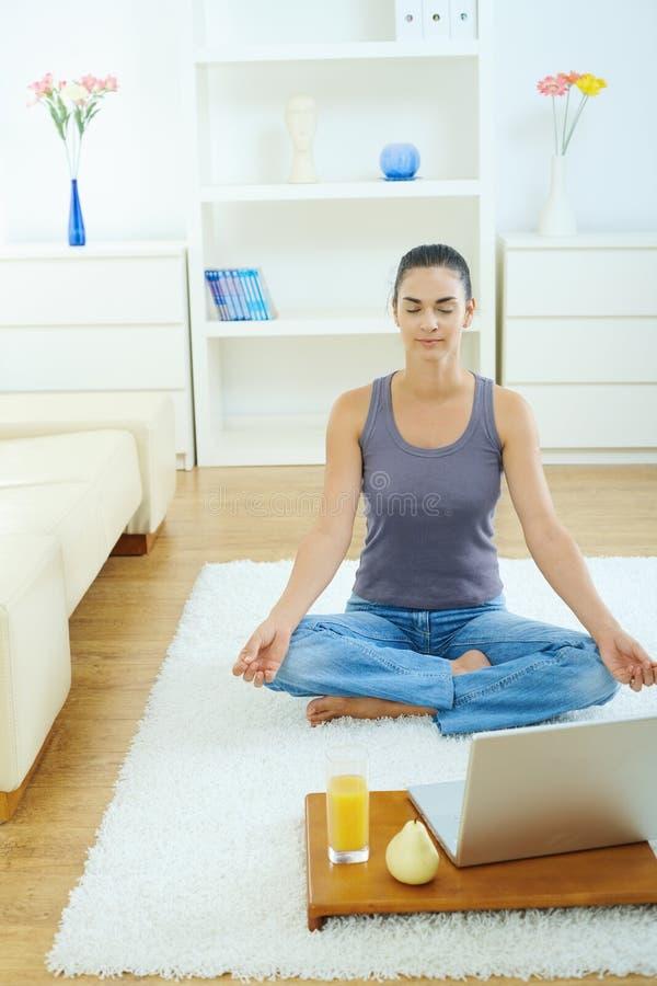 Frau, die zu Hause meditieren verwendet stockfoto