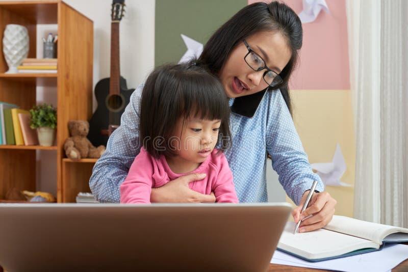 Frau, die zu Hause mit kleinem Mädchen arbeitet stockfotos