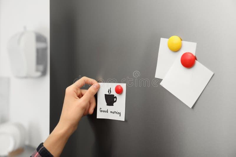 Frau, die zu Hause Papierblatt auf Kühlschranktür setzt lizenzfreies stockfoto