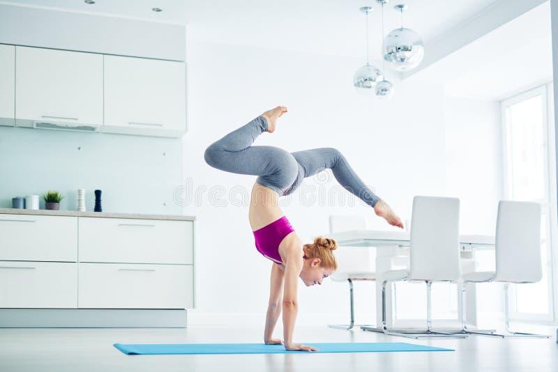 Frau, die zu Hause schöne Yoga-Haltung tut lizenzfreie stockbilder