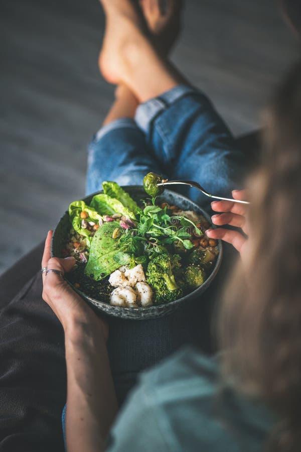 Frau, die zu Hause sitzt und superbowl des strengen Vegetariers isst lizenzfreies stockbild