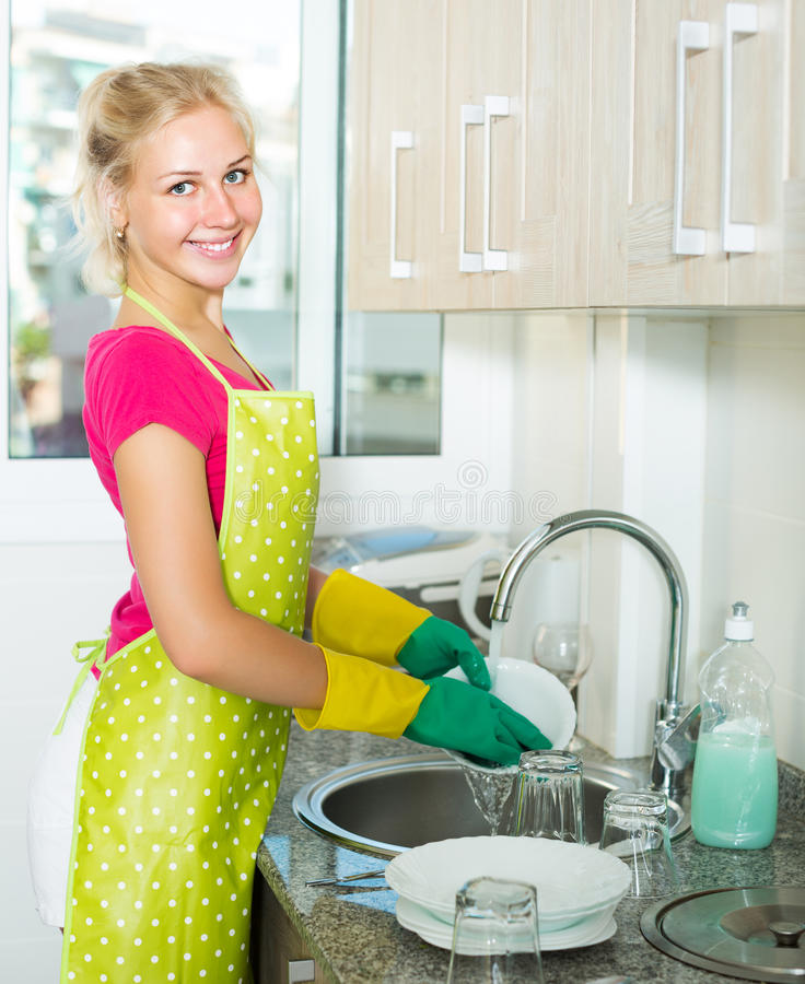 Frau, die zu Hause Teller tut stockfotos