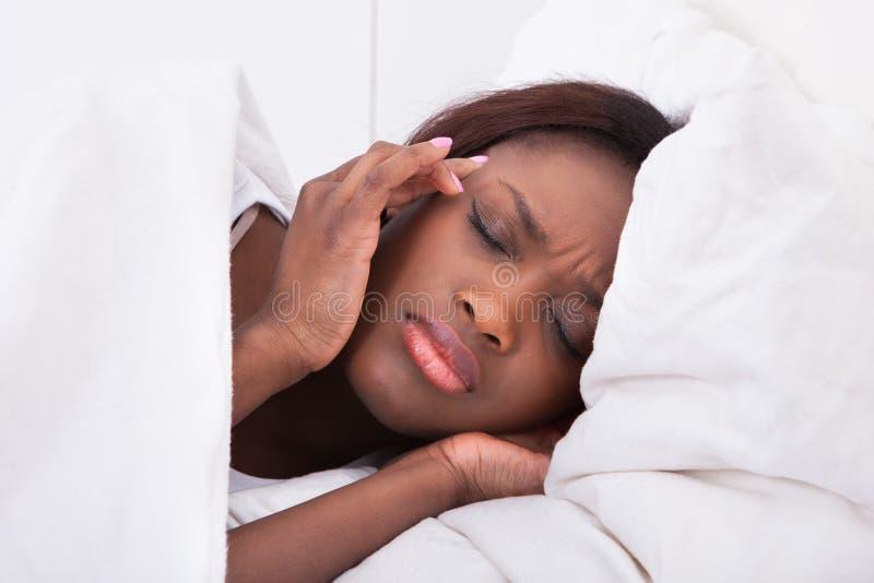 Frau, die zu Hause unter Kopfschmerzen im Bett leidet lizenzfreies stockbild