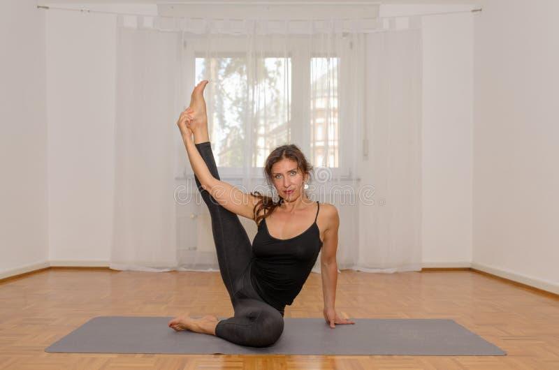 Frau, die zu Hause Yoga auf Matte ausübt stockfotografie
