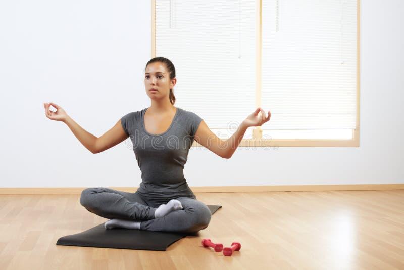 Frau, die zu Hause Yoga tut lizenzfreie stockbilder