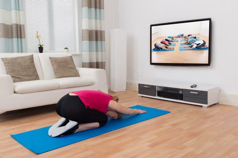 Frau, die zu Hause Yoga tut stockbilder