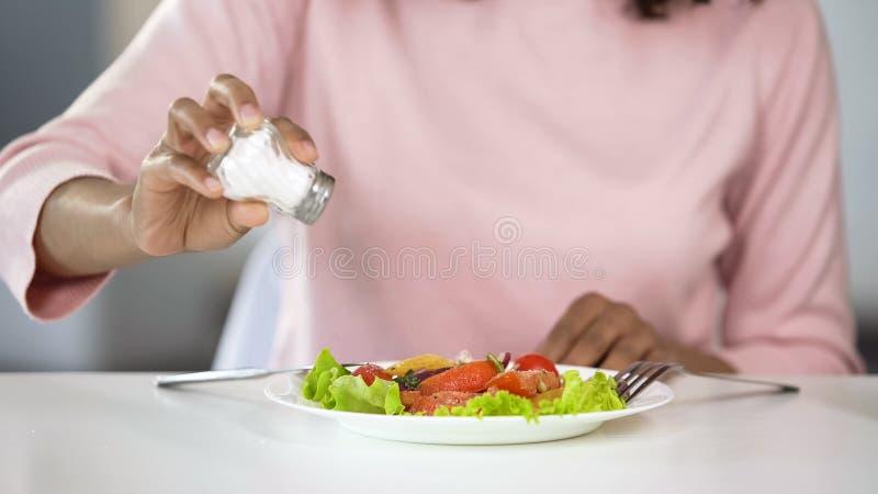 Frau, die zu viel Salz ihrem Lebensmittel, ungesundes Essen, Dehydrierungsprobleme hinzufügt lizenzfreie stockbilder
