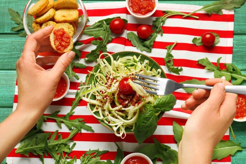 Frau, die Zucchinispaghettis mit Tomatensauce und Brot, Nahaufnahme isst lizenzfreie stockfotografie