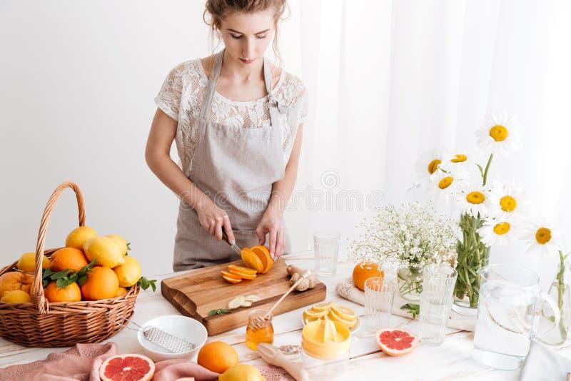 Frau, die zuhause der Orange geschnitten steht Beiseite schauen stockfoto
