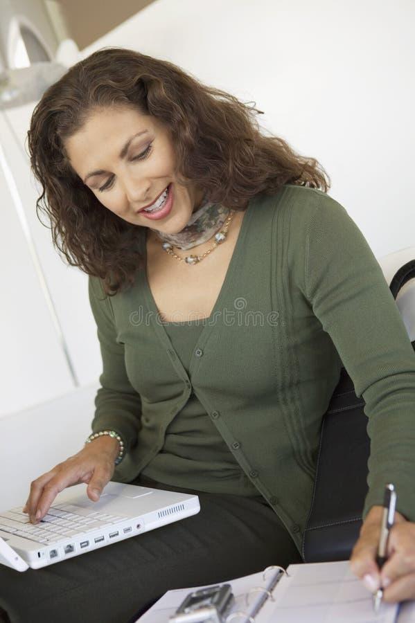 Frau, die zuhause Handy-Laptop und Organisator verwendet lizenzfreies stockbild