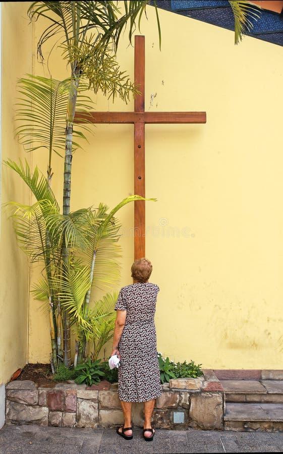 Frau, die zum Gott vor einem Kreuz betet Lima, Peru lizenzfreie stockbilder
