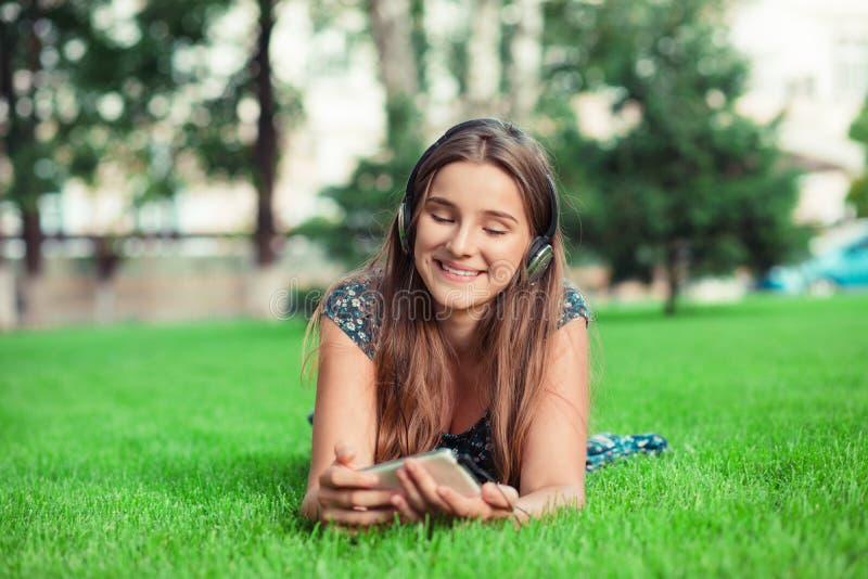 Frau, die zum Handy l?chelt im Freien sich hinlegt schaut stockfoto