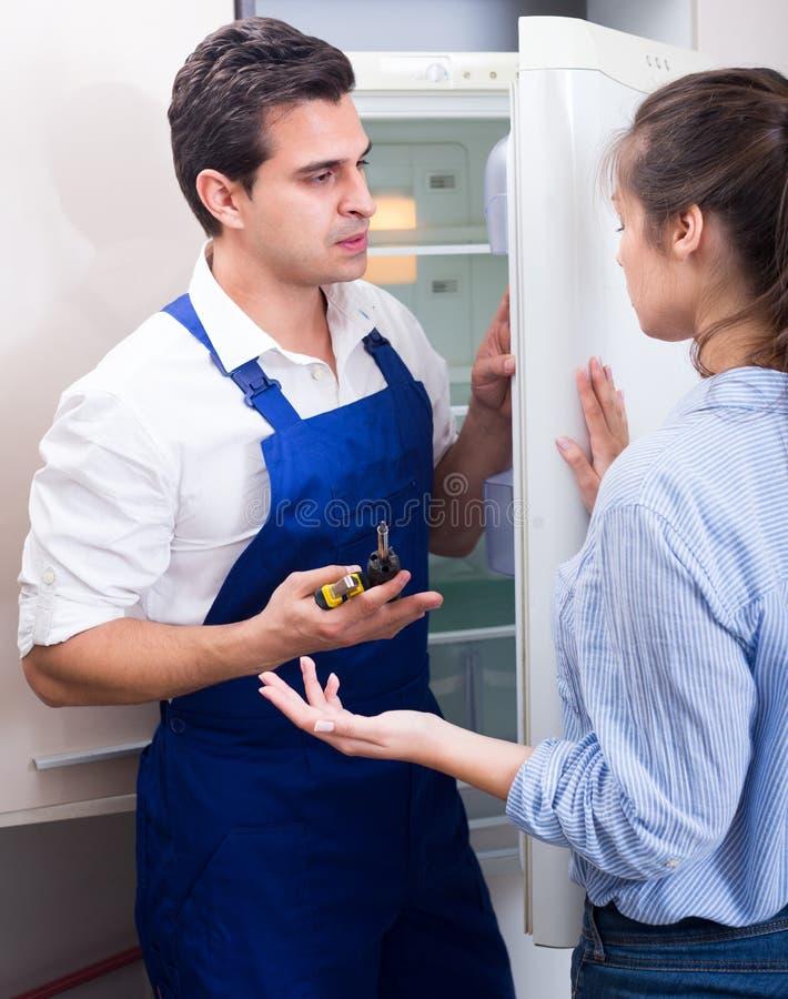 Frau, die zum Heimwerker auf Problemen sich beschwert stockfoto