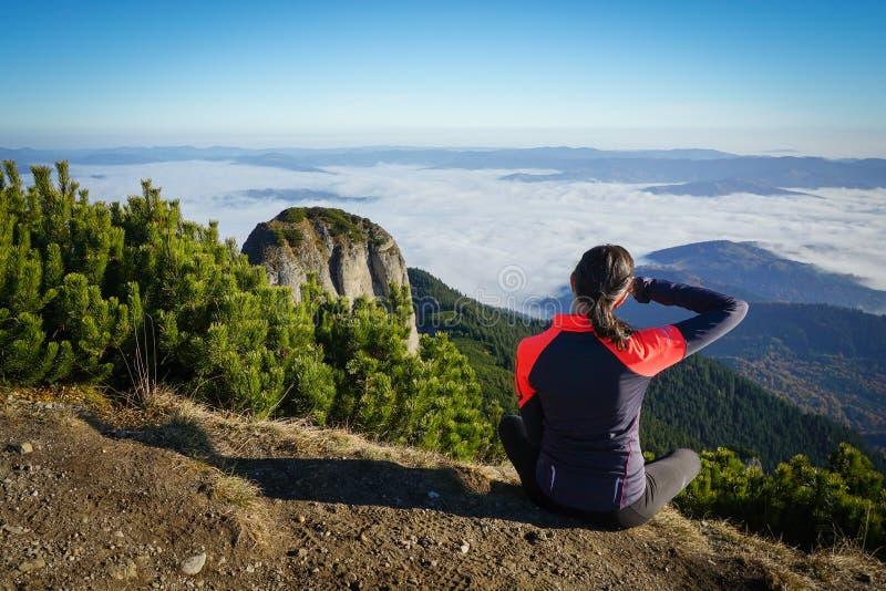 Frau, die zum Horizont in den Bergen schaut stockfotografie