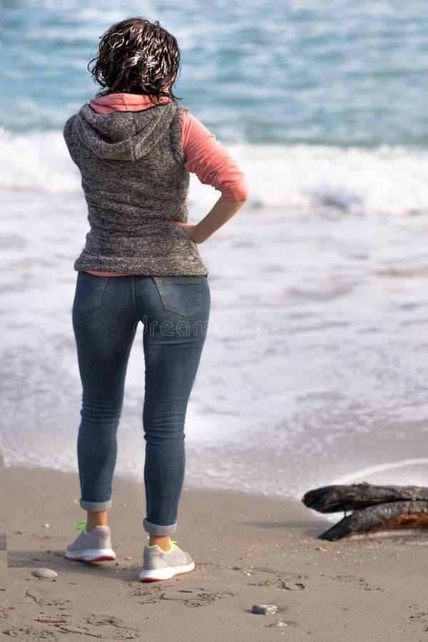 Frau, die zum Meer anstarrt stockfoto