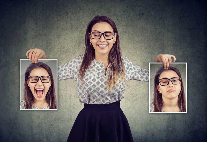 Frau, die zwei verschiedene Gesichtsgefühlmasken von hält lizenzfreies stockfoto