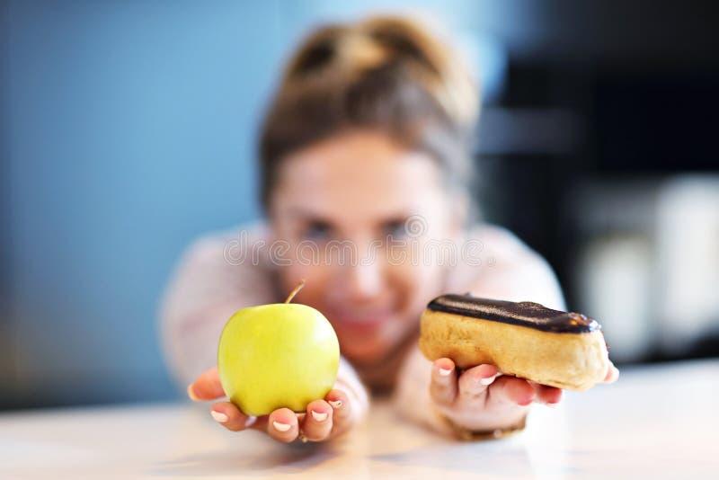 Frau, die zwischen Apfel und Eclair wählt stockbilder