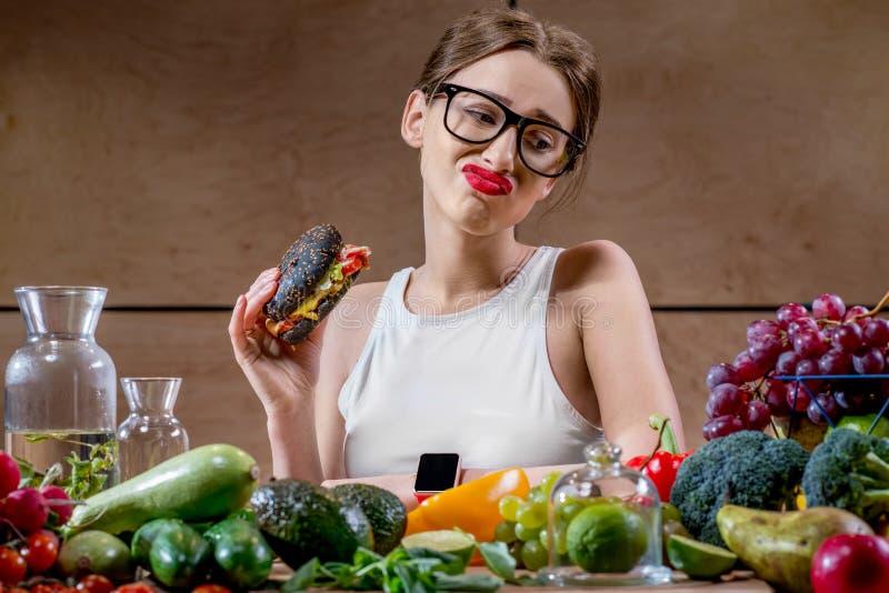 Frau, die zwischen Schnellimbiß und gesundem Gemüse, Früchte wählt lizenzfreies stockfoto