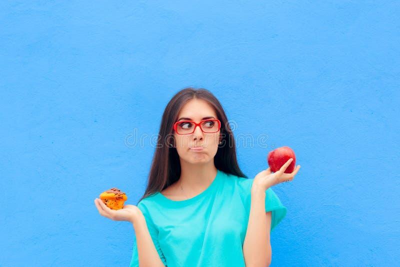Frau, die zwischen ungesundem Muffin und gesundem Apple wählt lizenzfreie stockfotos