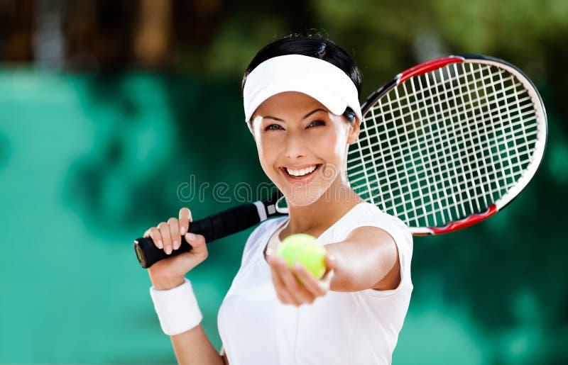 Frau dient Tenniskugel lizenzfreie stockbilder
