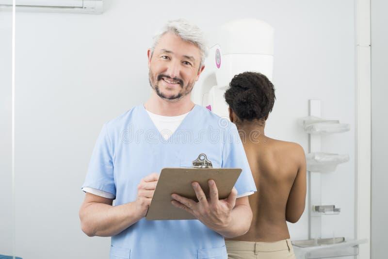 Frau Doktor-Holding Clipboard While, die Mammogramm-Röntgenstrahl durchmacht lizenzfreies stockbild