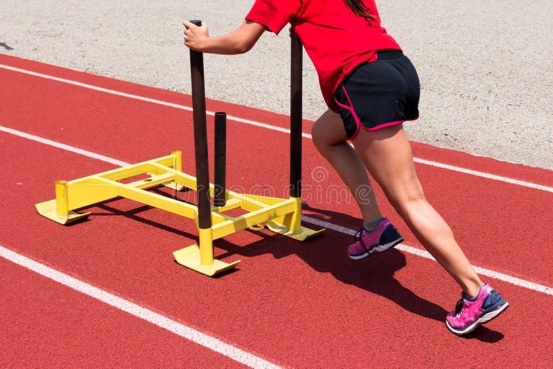 Frau drückt einen gelben Schlitten auf einer Bahn an der Praxis stockfoto