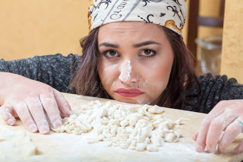 Frau drückt Sorge um ihre Vorbereitung von handgemachten Teigwaren aus. lizenzfreies stockbild