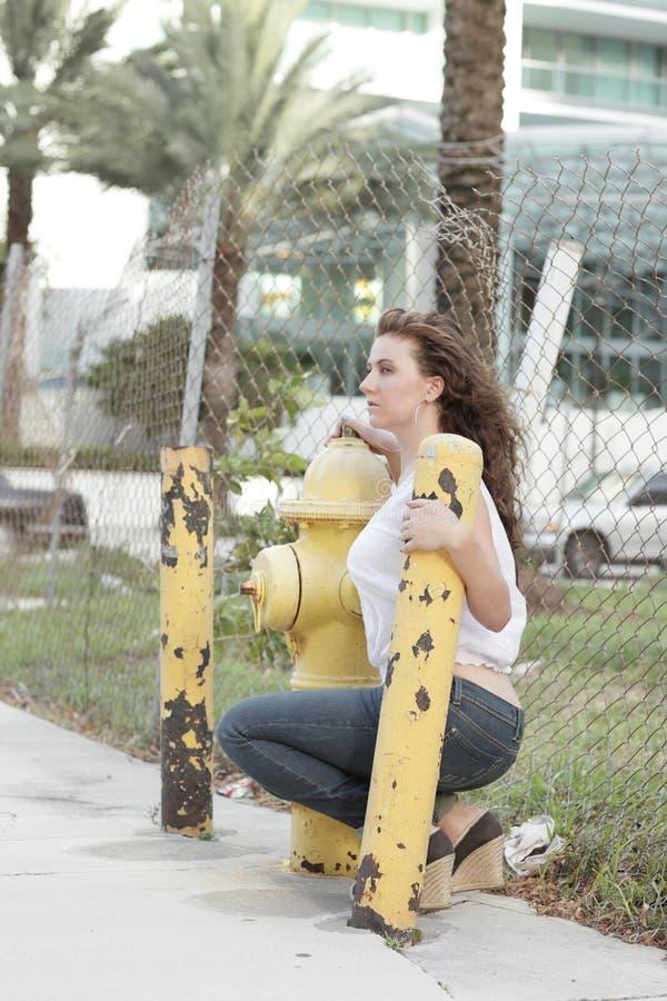 Frau durch einen Feuerhydranten stockfotos