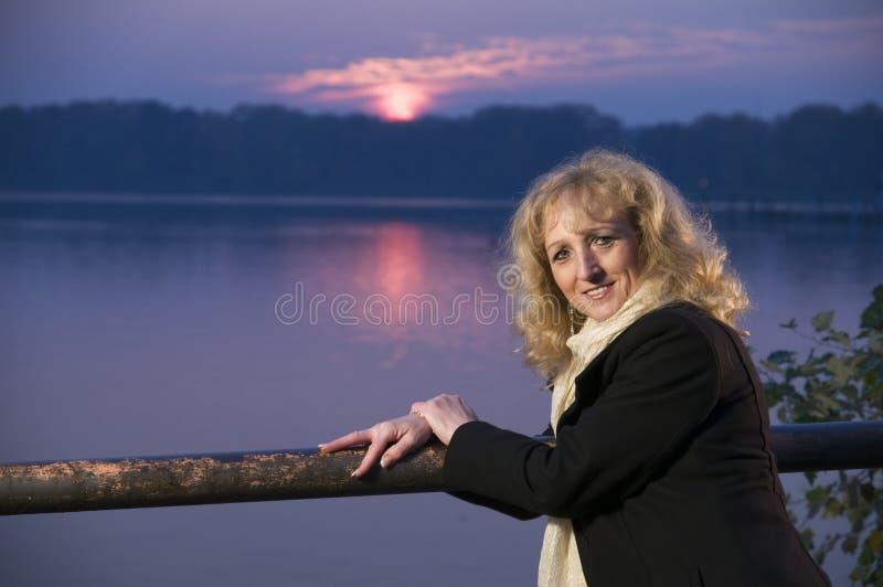 Frau durch See am Sonnenuntergang stockfotografie