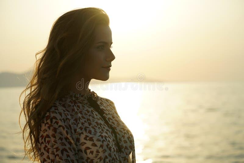 Frau durch Sonnenuntergang auf dem Strand stockfotografie