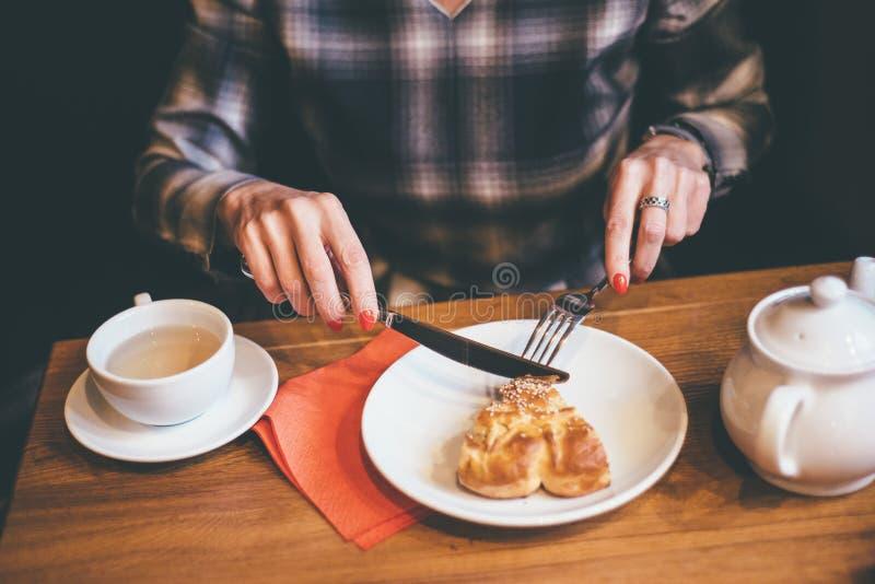 Frau eatting Torte und Getränkkaffee stockfoto