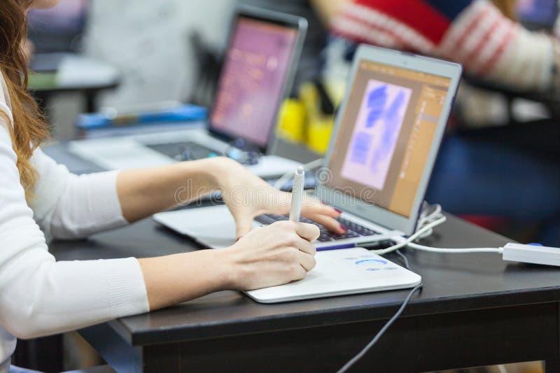 Frau eine Designerzeichnung im Laptop mit grafischer Tablette, Abschluss herauf Ansicht der Hand mit Stift stockbild