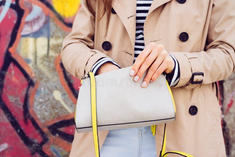Frau in einem beige Mantel und in einem gestreiften Hemd hält eine Handtasche auf einem bri stockfoto
