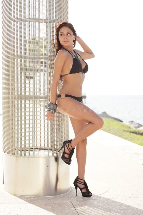 Frau in einem Bikini, der auf einer Metallstruktur sich lehnt stockbilder