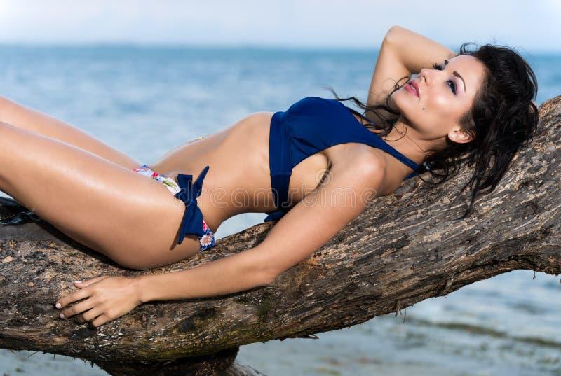 Frau in einem Bikini, der auf einer Niederlassung sich entspannt lizenzfreie stockfotos